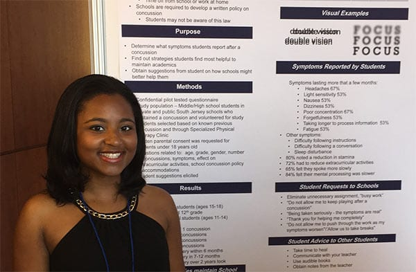Bria McKenzie with her poster at the American Occupational Health Conference
