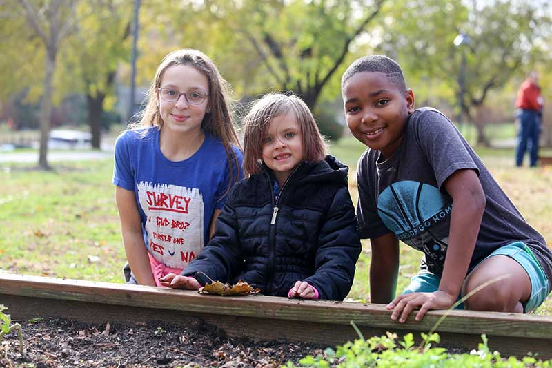 Fifth Grade Helps Kindergarteners Plant in Community Garden